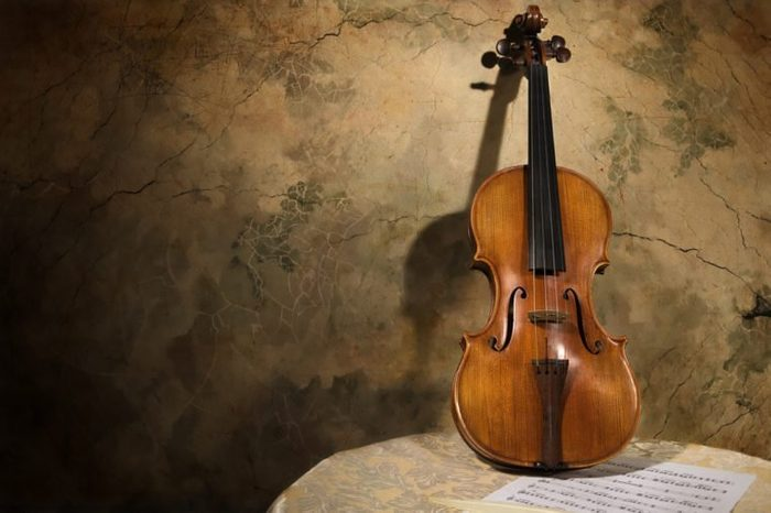 Picture of the old italian violin on a wall background
