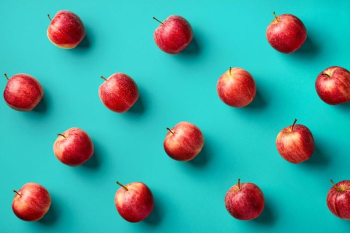 Colorful fruit pattern of fresh red apples on blue background. From top view