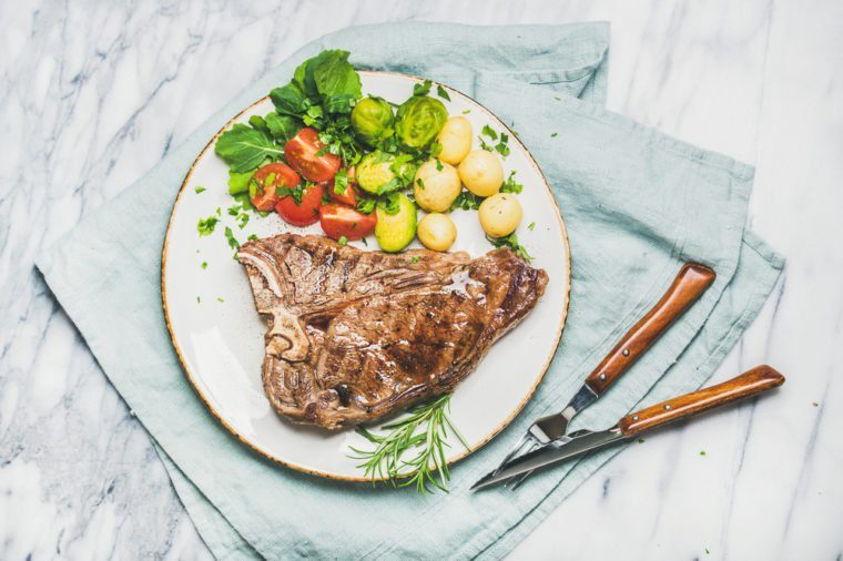 Grilled meat dinner plate. Cooked beef tbone steak with vegetables and fresh rosemary over marble table background, top view