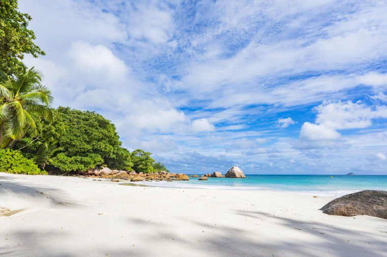 Turquoise water, granite rocks and palm trees in the white sand on the paradise beach at anse lazio on the seychelles