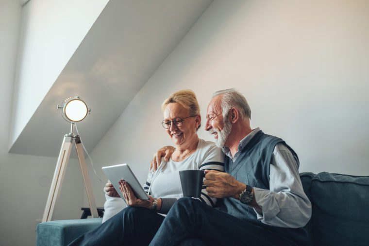 Elderly couple holding a digital tablet laughing