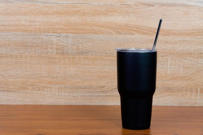 Black colour stainless steel tumbler or cold storage cup with water straw and cap on wooden background.