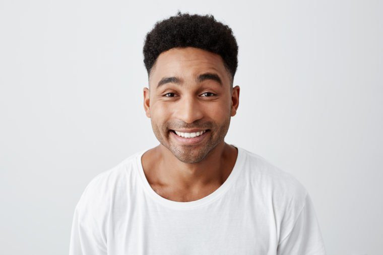 Close up isolated portrait of cheerful happy young man with afro hairstyle in casual white t-shirt smiling brightly, looking in camera with excited and joyful expression.