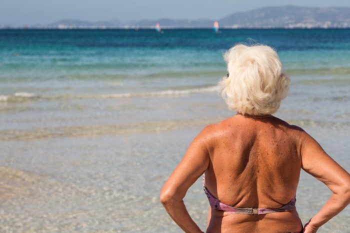 Senior woman standing alone in front of the sea / ocean at a beach in a sunny summer day. Older female looking out to the sea and enjoying retirement. Winter getaway concept.
