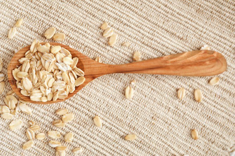 Oatmeal flakes and wooden spoon on fabric
