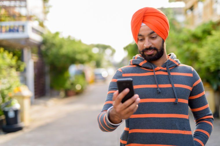 Portrait of young handsome Indian Sikh man wearing turban in the streets outdoors