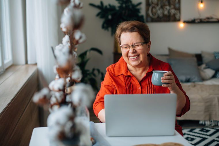 laughing Senior woman using laptop for websurfing. Mature lady with cup of coffee watching funny movie.