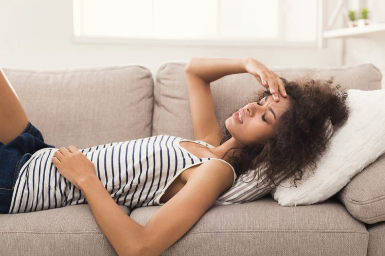 Sad girl with headache. Young african-american woman feeling pain, lying on sofa at home, copy space