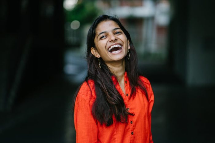 Attractive and young Indian woman smiling against a city background. She's wearing an ethnic orange outfit dress.