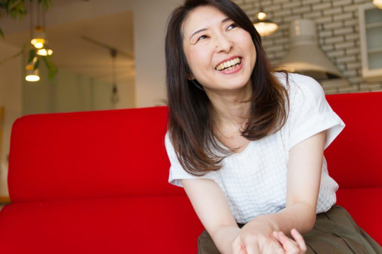 Japanese woman laughing at living room, sitting on red sofa