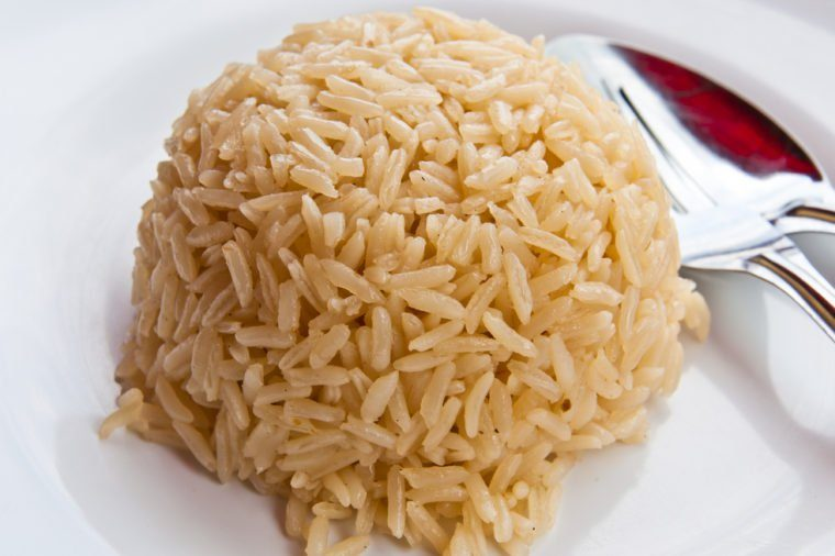 White rice on a plate, spoon on the side