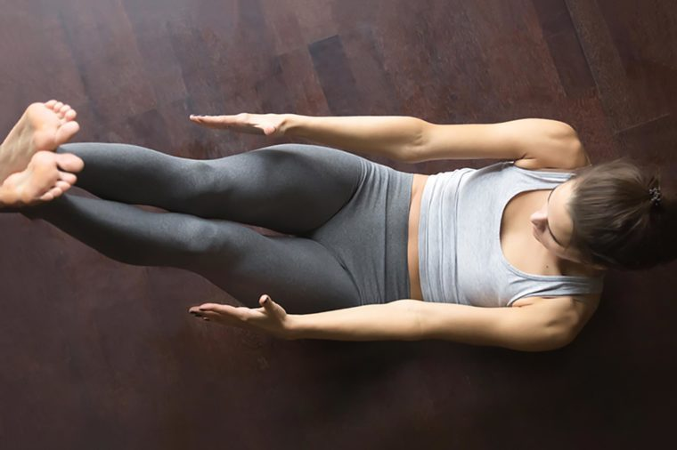 Beautiful young model working out at home, doing fitness exercise on floor, Paripurna Navasana for upper and lower abs, Full Boat pose. Core training. Top view. Full length