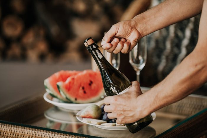 Hands twist the muse on a bottle of sparkling wine. Back on the glass table a plate with watermelon and fruit