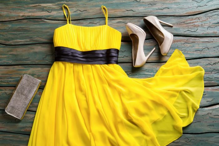 Yellow dress and silver purse. Beige heel shoes and bag. Woman's clothing on green shelf. Outfit with handy accessory.