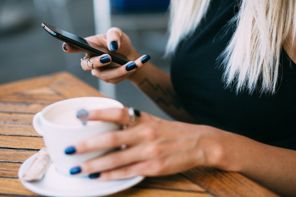 Close up of hip young woman using phone in cafe