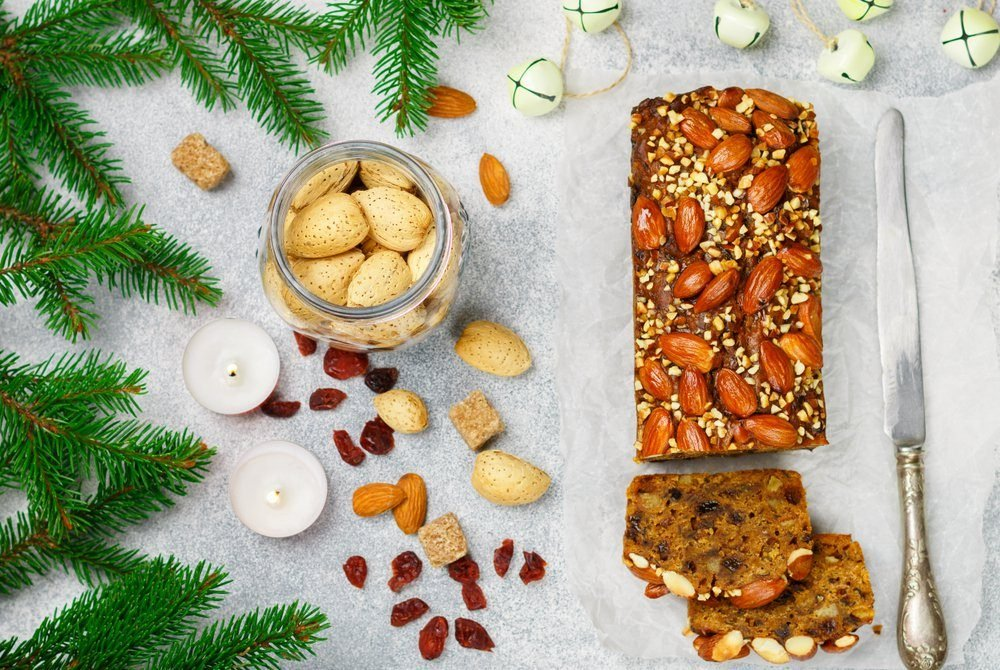 Fruitcake. Traditional Christmas cake with almonds, dried cranberries, raisins, cinnamon, cardamom, anise, cloves. Pudding. New year. Selective focus. Top view and copy space