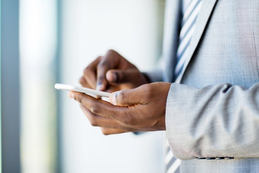 close up of african businessman hands texting on smart phone