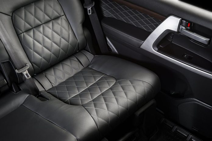Back passenger seats in modern luxury car, frontal view, perforated black leather with stitching