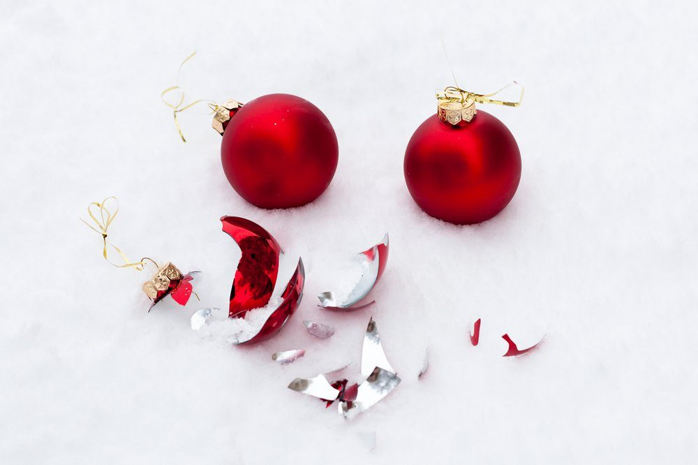 Two whole Christmas toys and shattered red Christmas toy lies on white snow