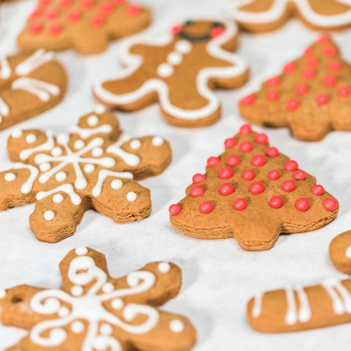 Decorating traditional gingerbread cookies with royal icing for Christmas.