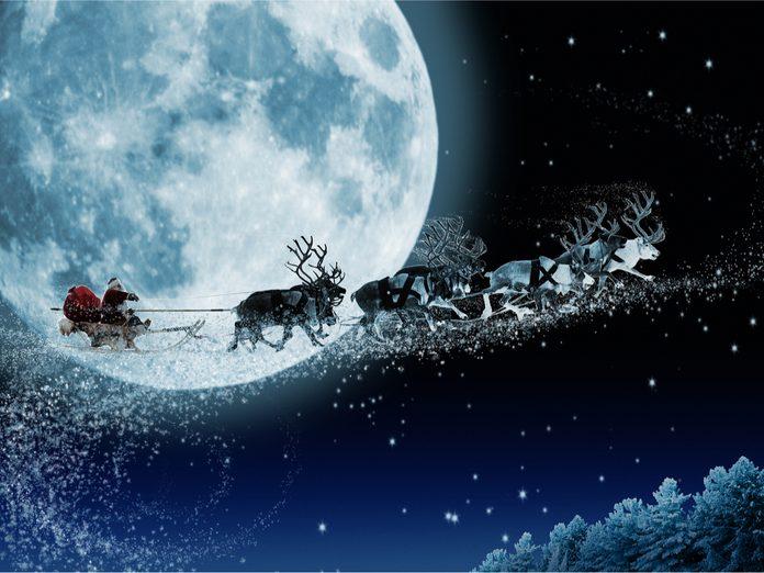 Santa and reindeer in front of moon