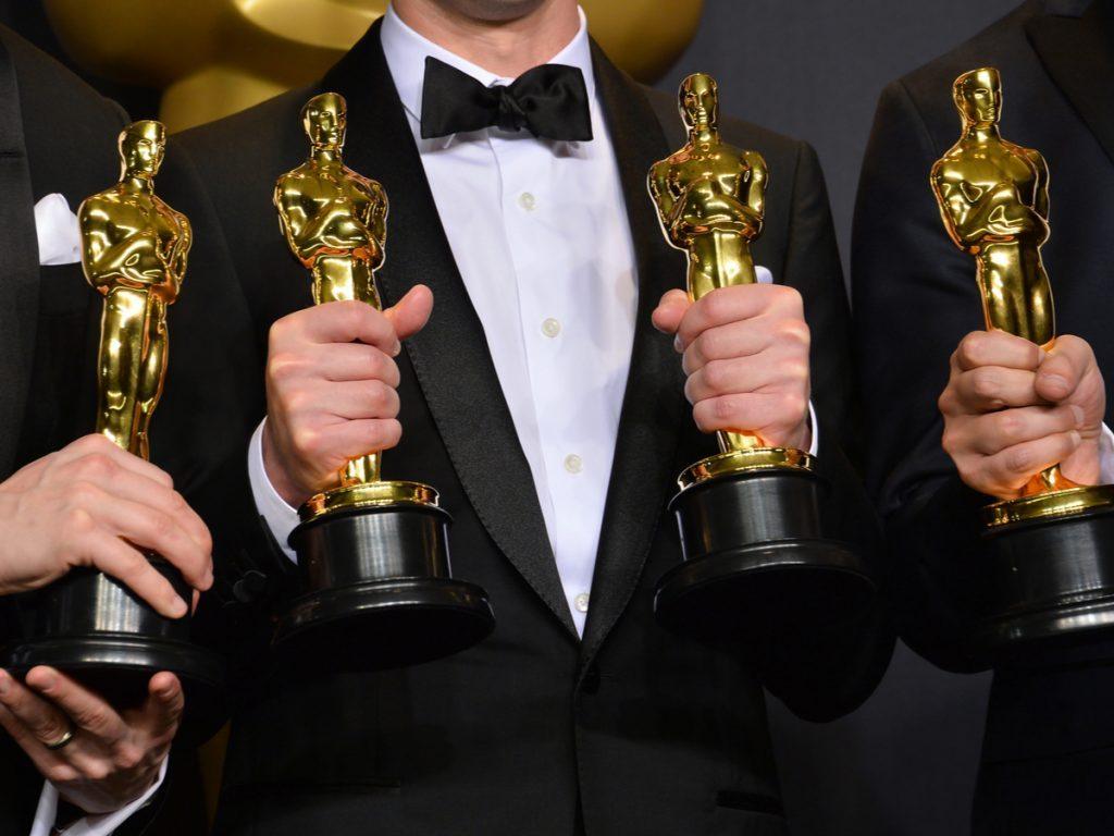 People holding Oscars