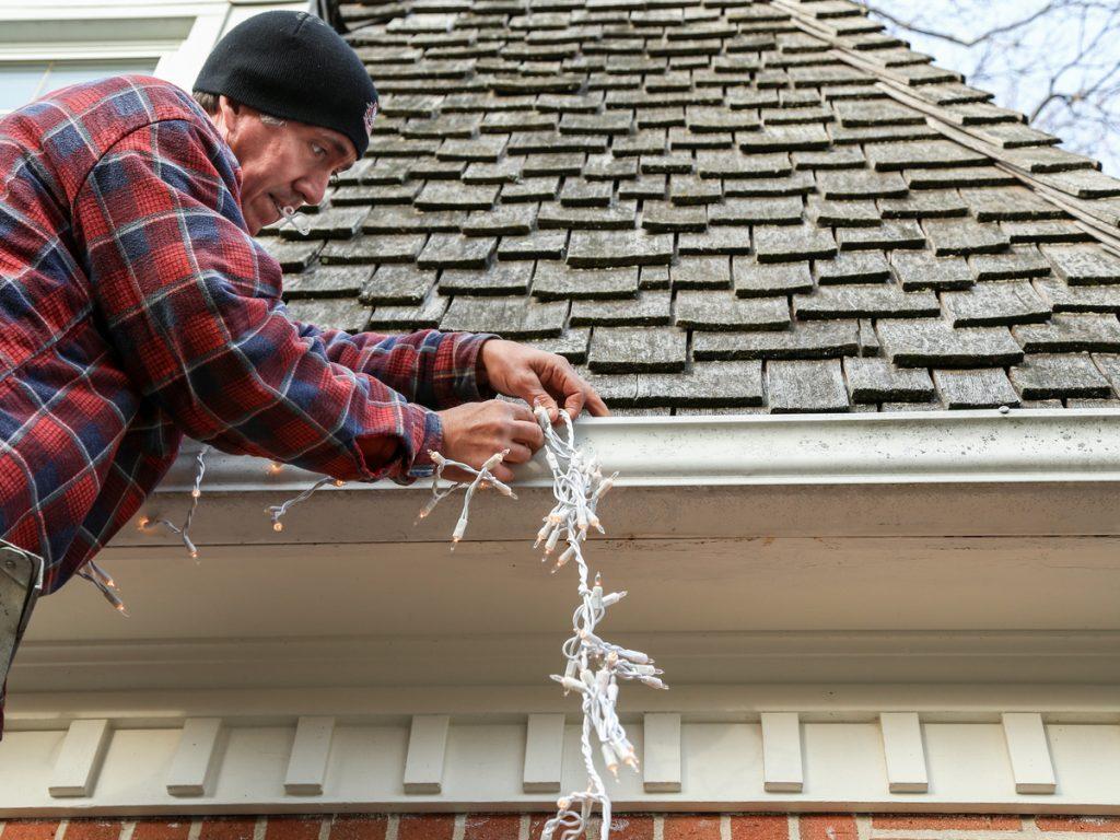 Man putting Christmas lights on roof
