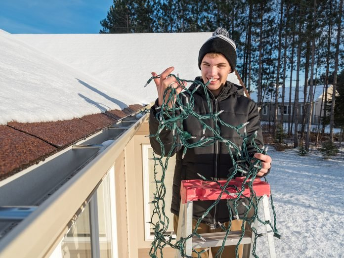 Person putting up Christmas lights