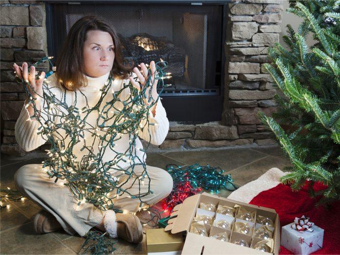 Woman untangling Christmas lights