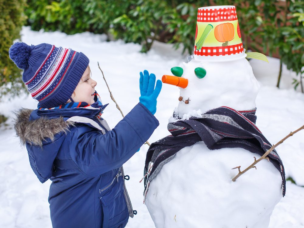 Kid decorating snowman