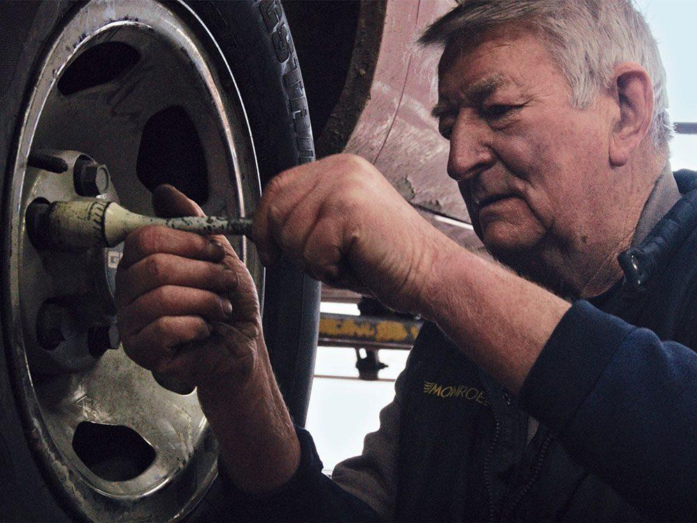 Senior man repairing car wheels