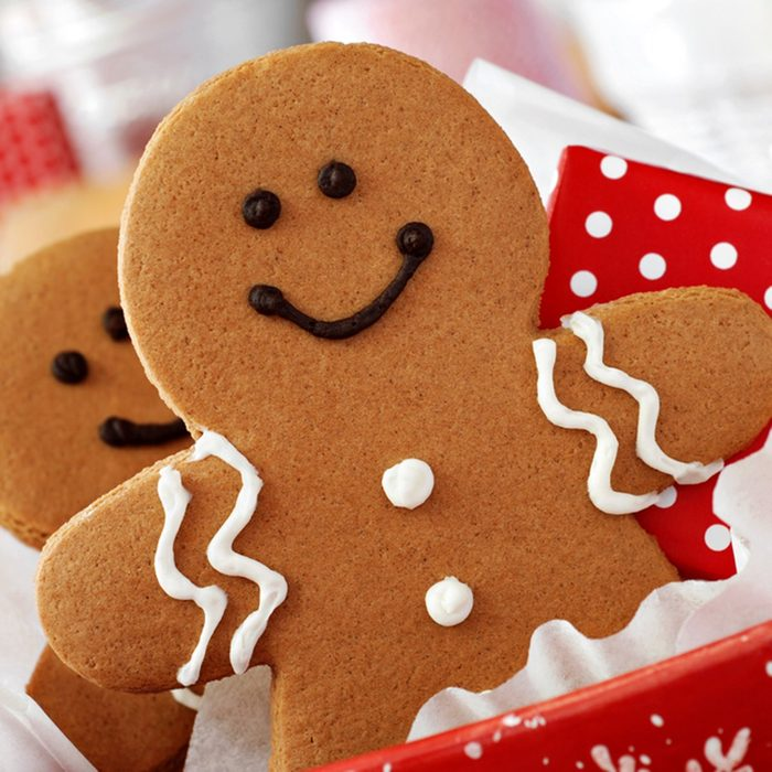 Smiling gingerbread men nestled in holiday dish with gift-wrapped surprise.