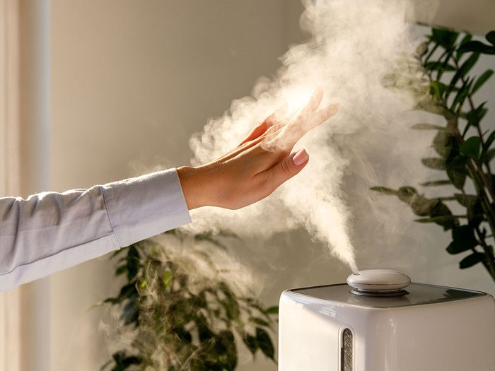 Humidifier hack - Woman holds hand over steam aroma oil diffuser on the table at home