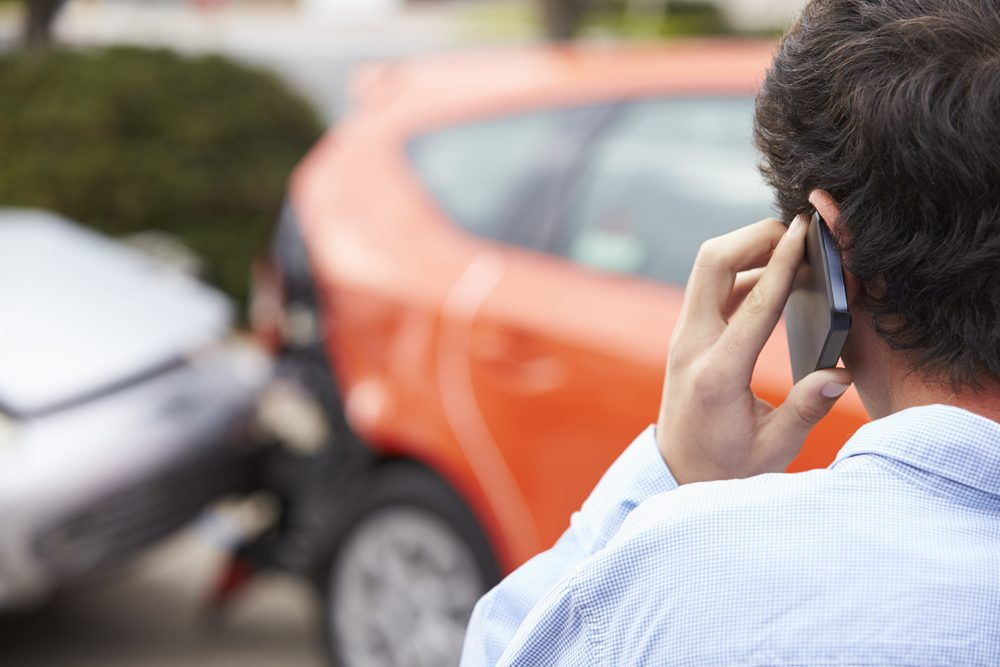 Teenage Driver Making Phone Call After Traffic Accident