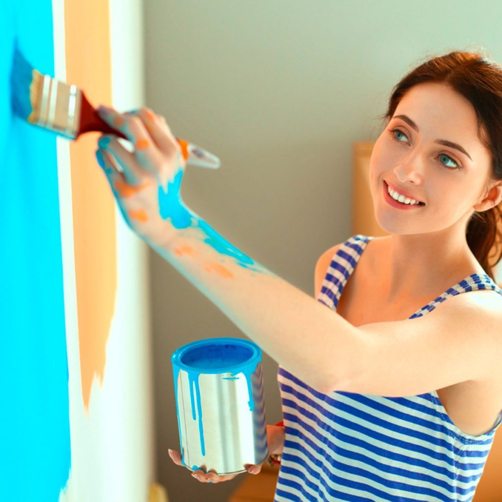 Attractive woman painting bedroom wall