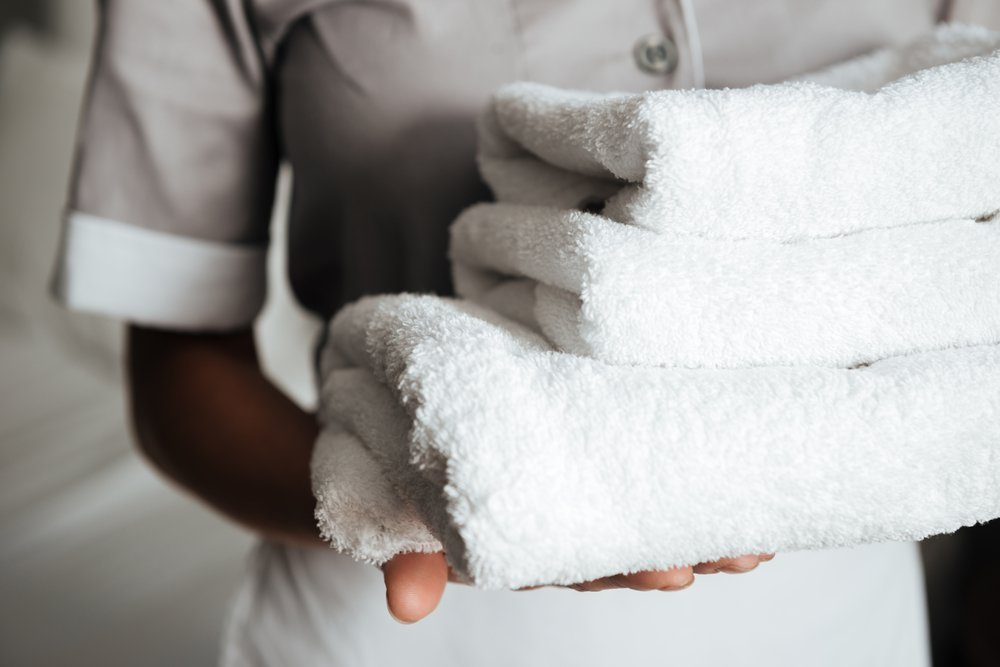 Close up of a young hotel maid holding clean folded towels