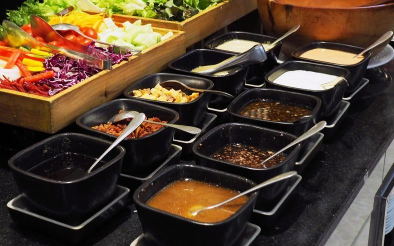 Colorful fresh vegetables prepared for chosen in salad bar buffet line with various kind of salad dressing.