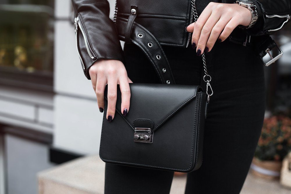 Young stylish beautiful woman walking in street, wearing pink trendy leather jacket, holding purse, black shirt, fashion outfit, autumn trend, spring fashion,accessories, hands close-up,copy space.