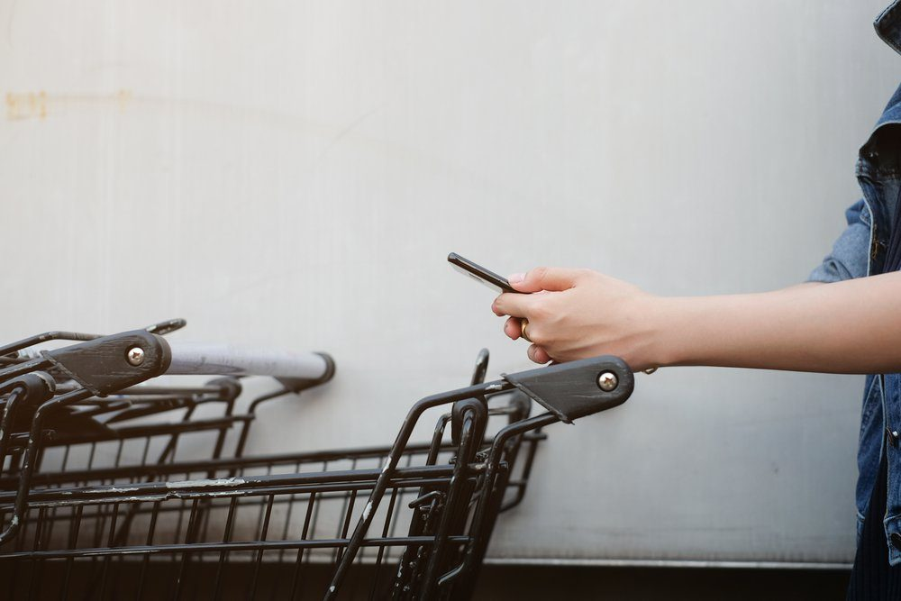 close up asian woman hand using smart phone and holding trolley bar for shopping on cement background at outside mall concept.