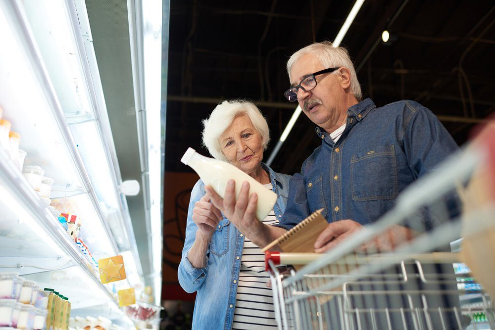 Low angle portrait of modern senior couple choosing milk standing by dairy isle in supermarket while grocery shopping, copy space