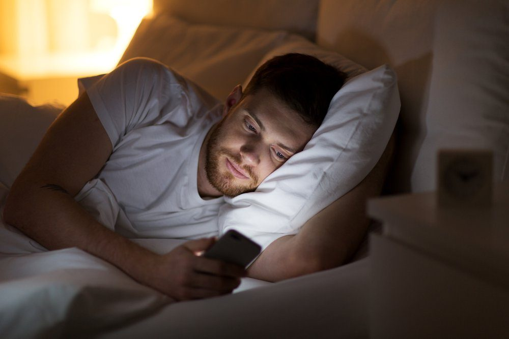 technology, internet, communication and people concept - happy smiling young man texting on smartphone in bed at home at night