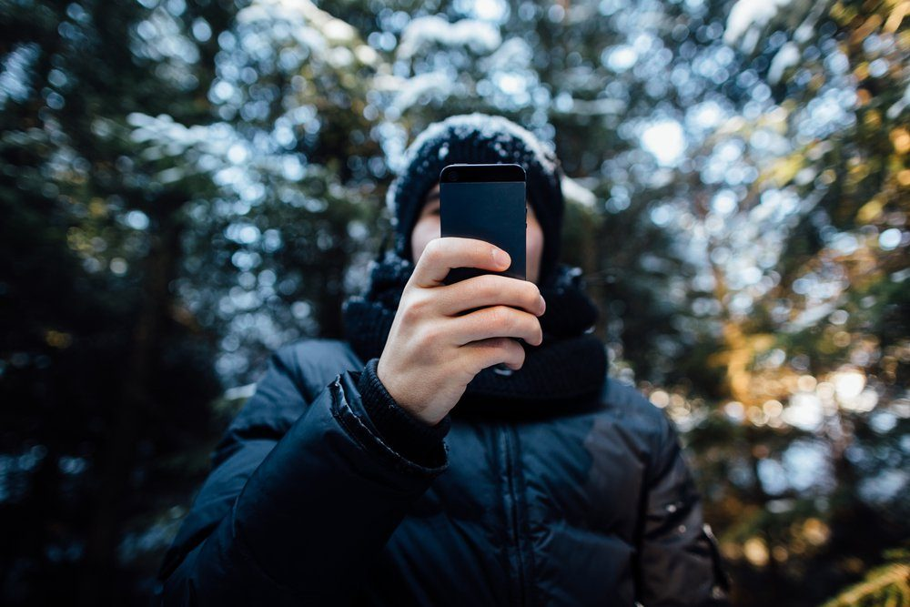 Man takes a picture on mobile phone in the snow-covered pine forest on a cold winter day