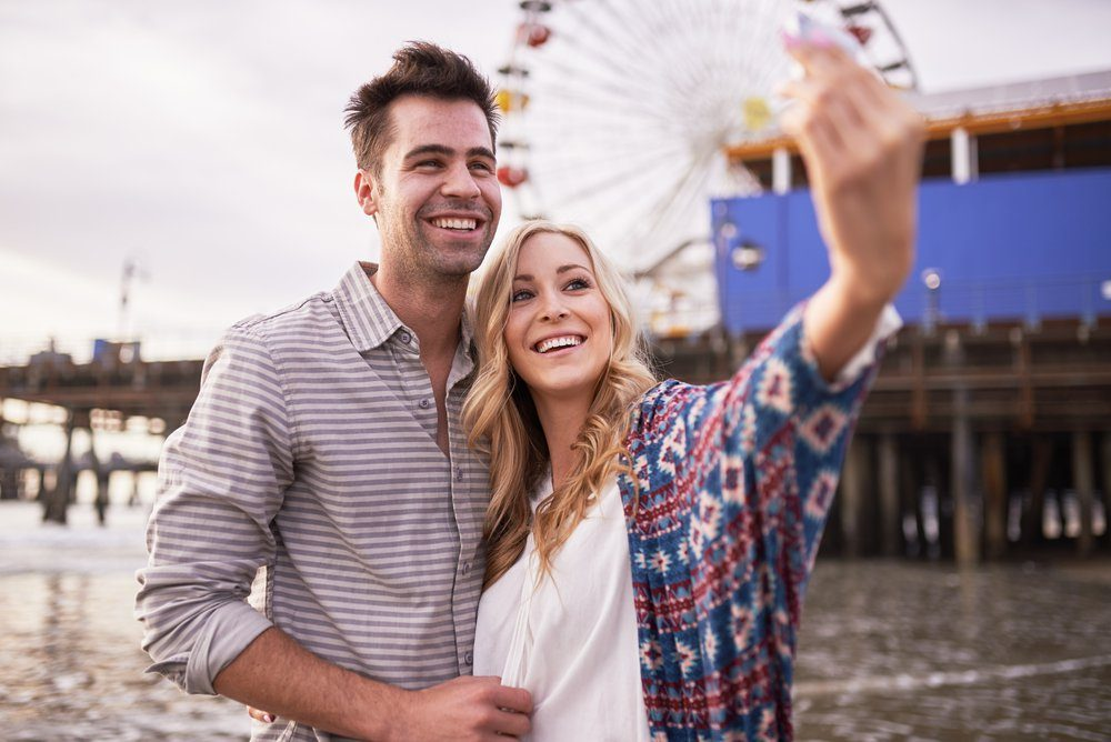 romantic couple taking selfies together in santa monica