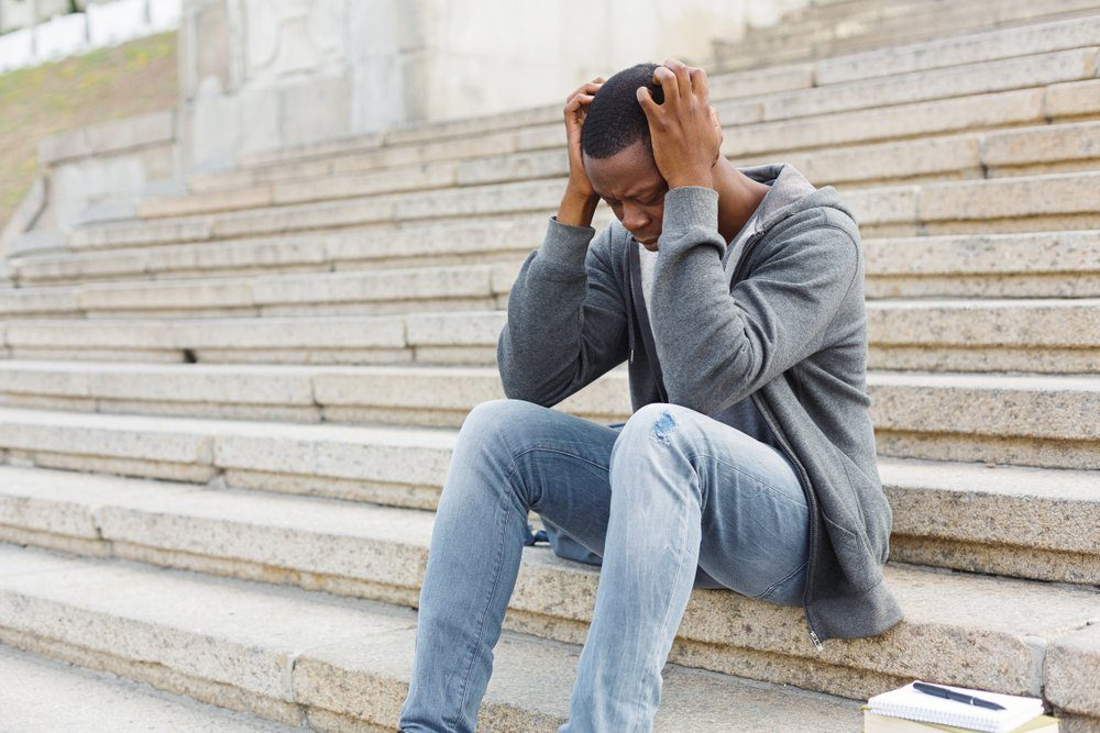 Stressed african-american man sitting alone with headache at university on stairs. Black depressed student guy failed exams, expelled from college, copy space
