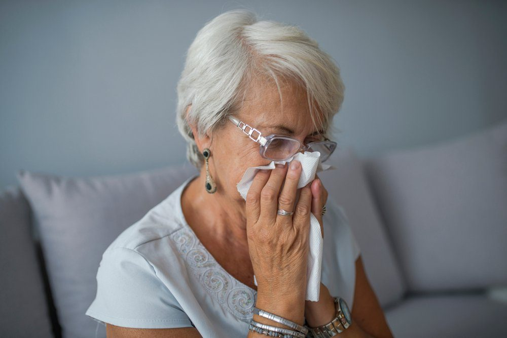 Senior Woman Blowing Nose With Tissue At Home. Sick mature woman catch cold. Sneezing with handkerchief, coughing, got flu, having runny nose. I need some immune system support