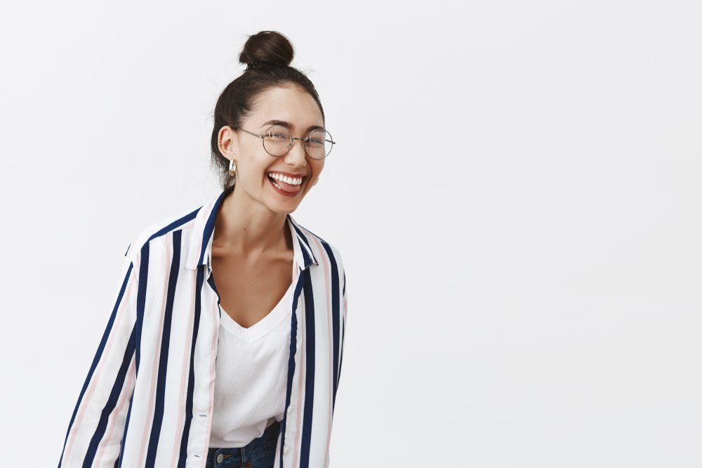 Girl just wanna have fun. Studio shot of charming playful woman leading active and happy lifestyle, bending towards camera while laughing over funny joke, standing in trendy outfit and glasses
