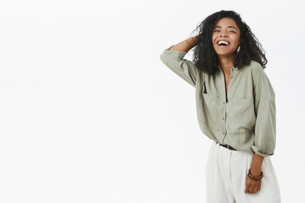 Indoor shot of carefree delighted and happy creative african american woman in trendy shirt and pants holding hand on hair and laughing joyfully spending amused time in funny company over gray wall