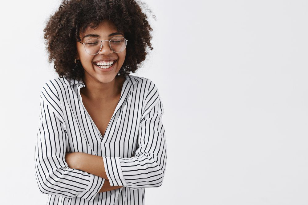 Belly aching from laughter. Amused and carefree attractive african american woman in striped blouse and glasses closing eyes laughing out loud and holding hands on chest closing eyes having fun