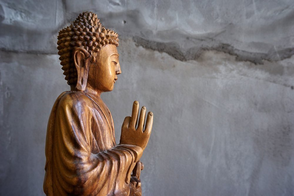Wooden buddha statue, on grey cement background