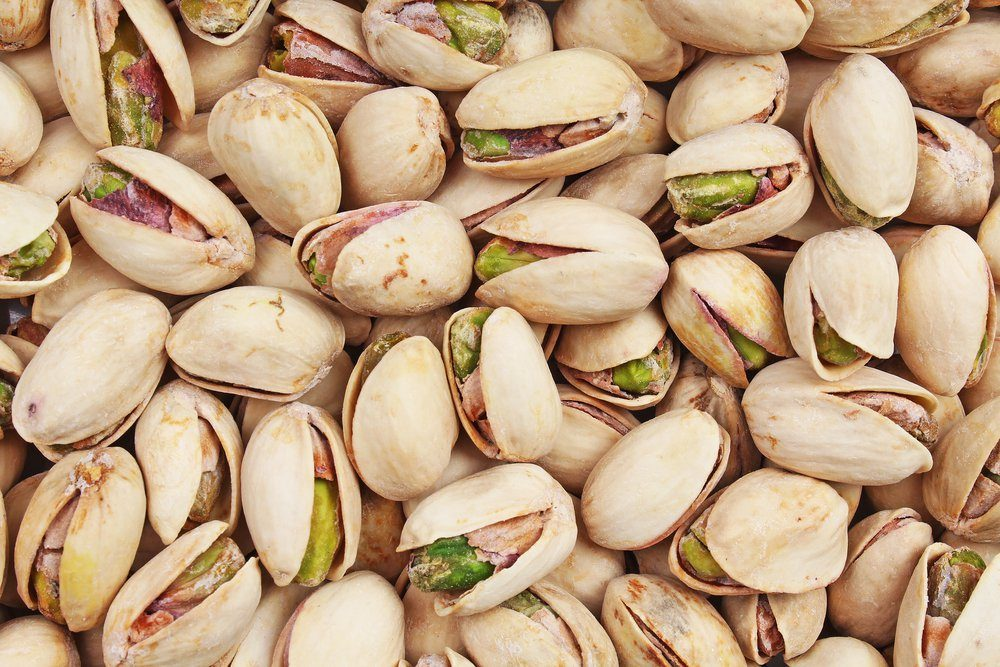 Pistachio texture. Nuts. Green fresh pistachios as texture. Roasted salted pistachio nuts healthy delicious food studio photo.